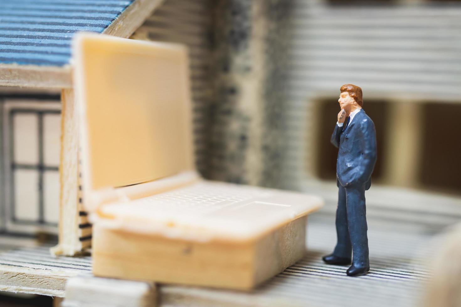 miniatuurzakenman die met een computerlaptop werken, thuiswerkconcept foto