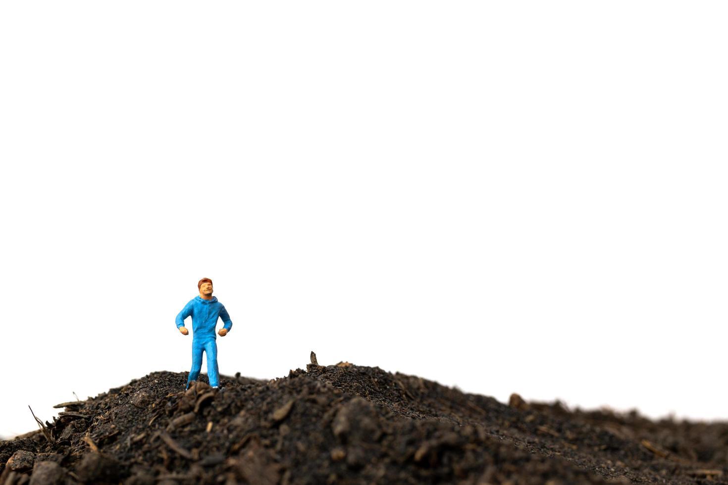 miniatuur man loopt op de grond geïsoleerd op een witte achtergrond, rennen voor gezondheid concept foto