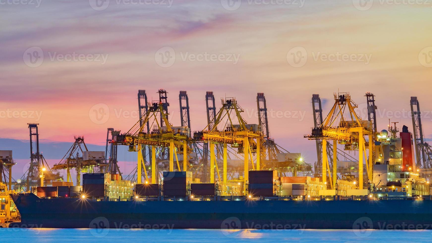 vrachtschip dat lading laadt bij laaddok in singapore bij schemering foto