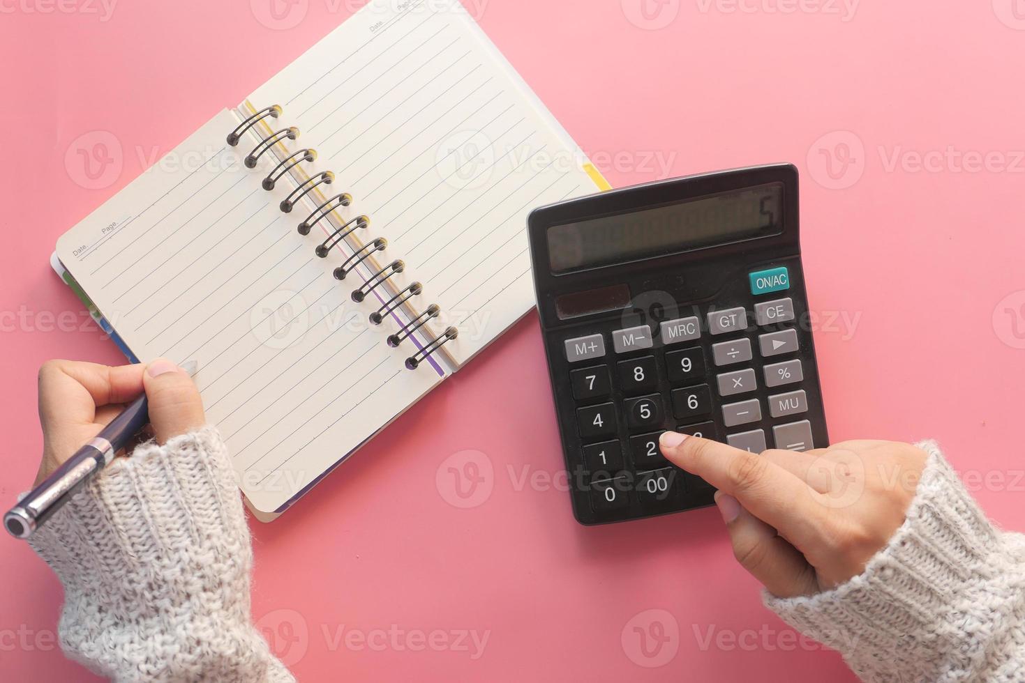 vrouwen hand met behulp van rekenmachine op roze achtergrond foto