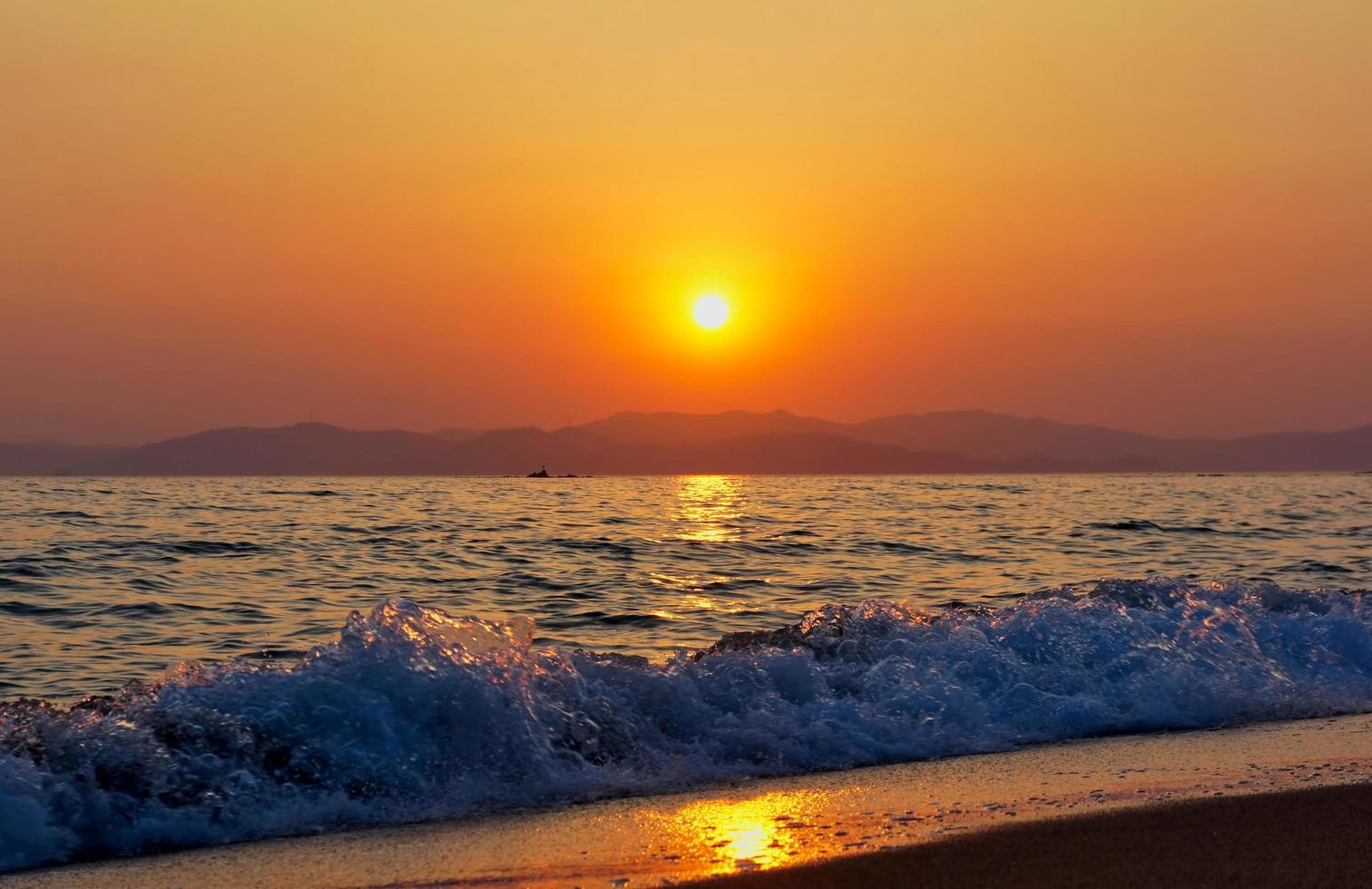 golven die breken op een strand met oranje bewolkte zonsondergang over bergen foto