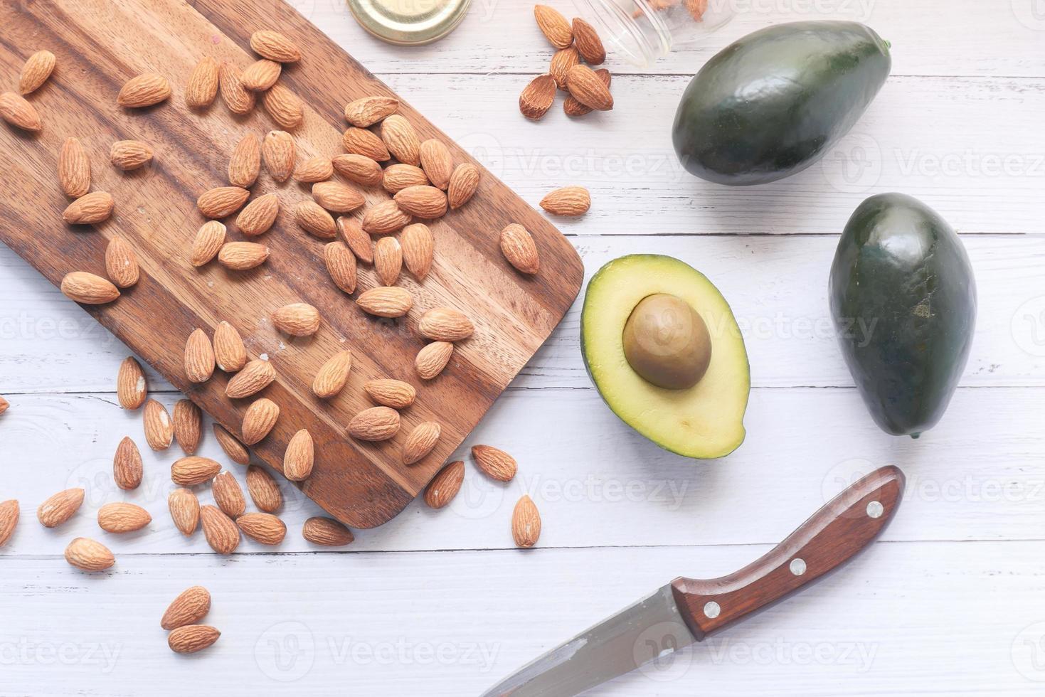 plakje avocado en amandelen op een snijplank foto