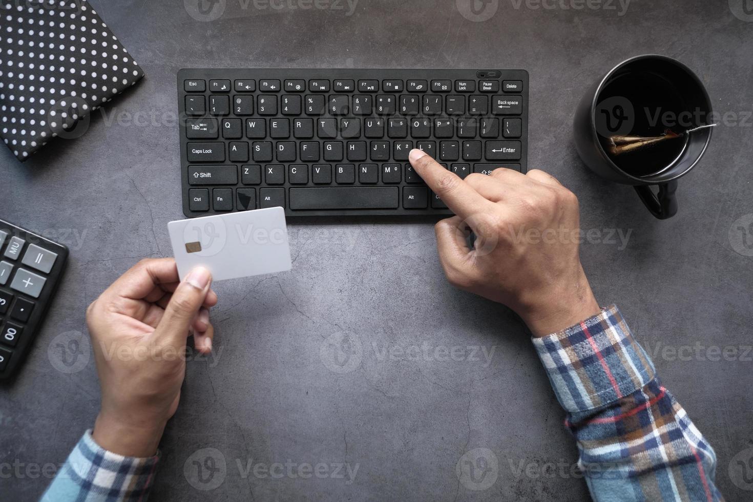 bovenaanzicht van man creditcardgegevens invoeren op computer foto