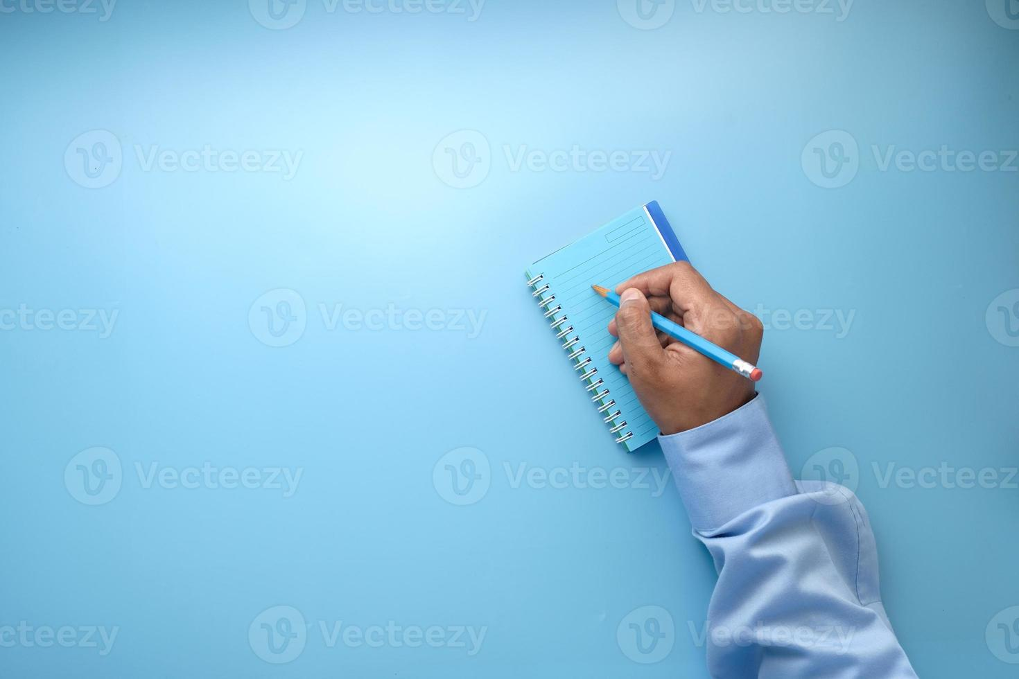 hand schrijven in Kladblok op blauwe achtergrond foto