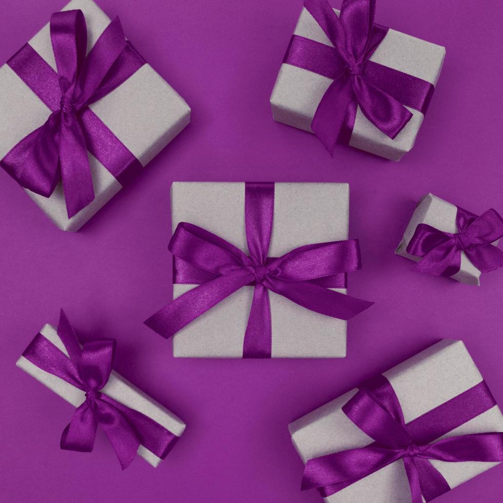 geschenkdozen verpakt in ambachtelijk papier met paarse linten en strikken, feestelijke zwart-wit plat leggen foto