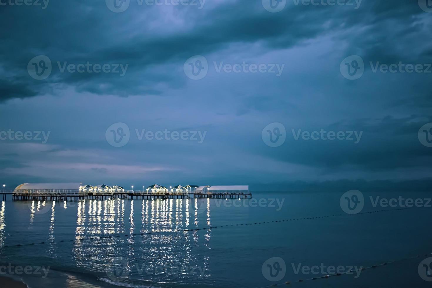 schemering landschap van pier die zich uitstrekt in zee foto