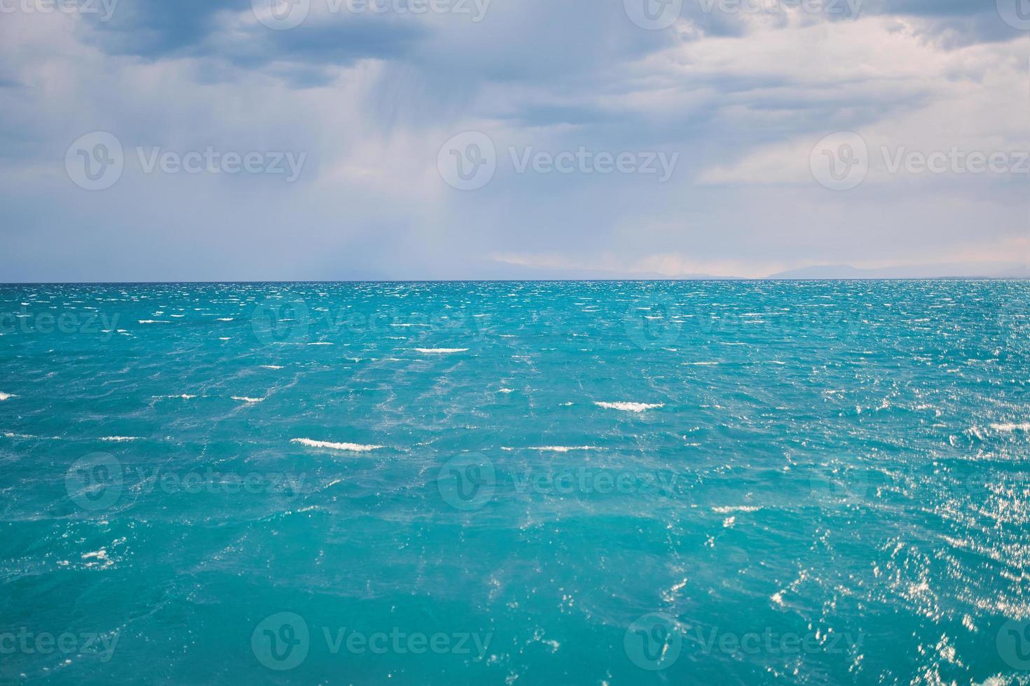 zeegezicht met duidelijke horizonlijn en bewolkte hemel foto