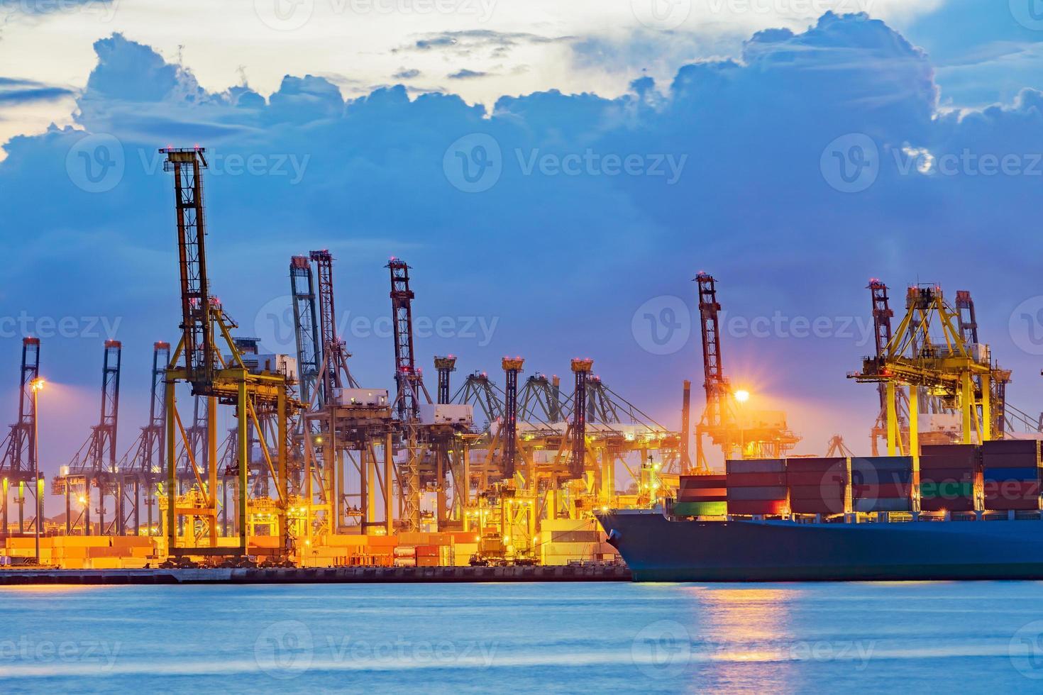 vrachtschip dat lading laadt bij laaddok op schemertijd. foto