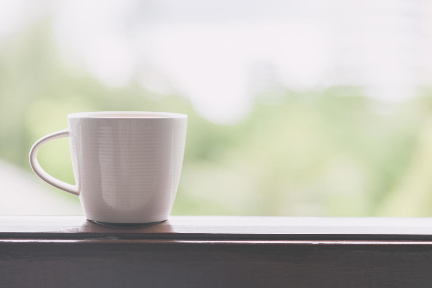 witte koffiekopje met uitzicht naar buiten - vintage filtereffect foto