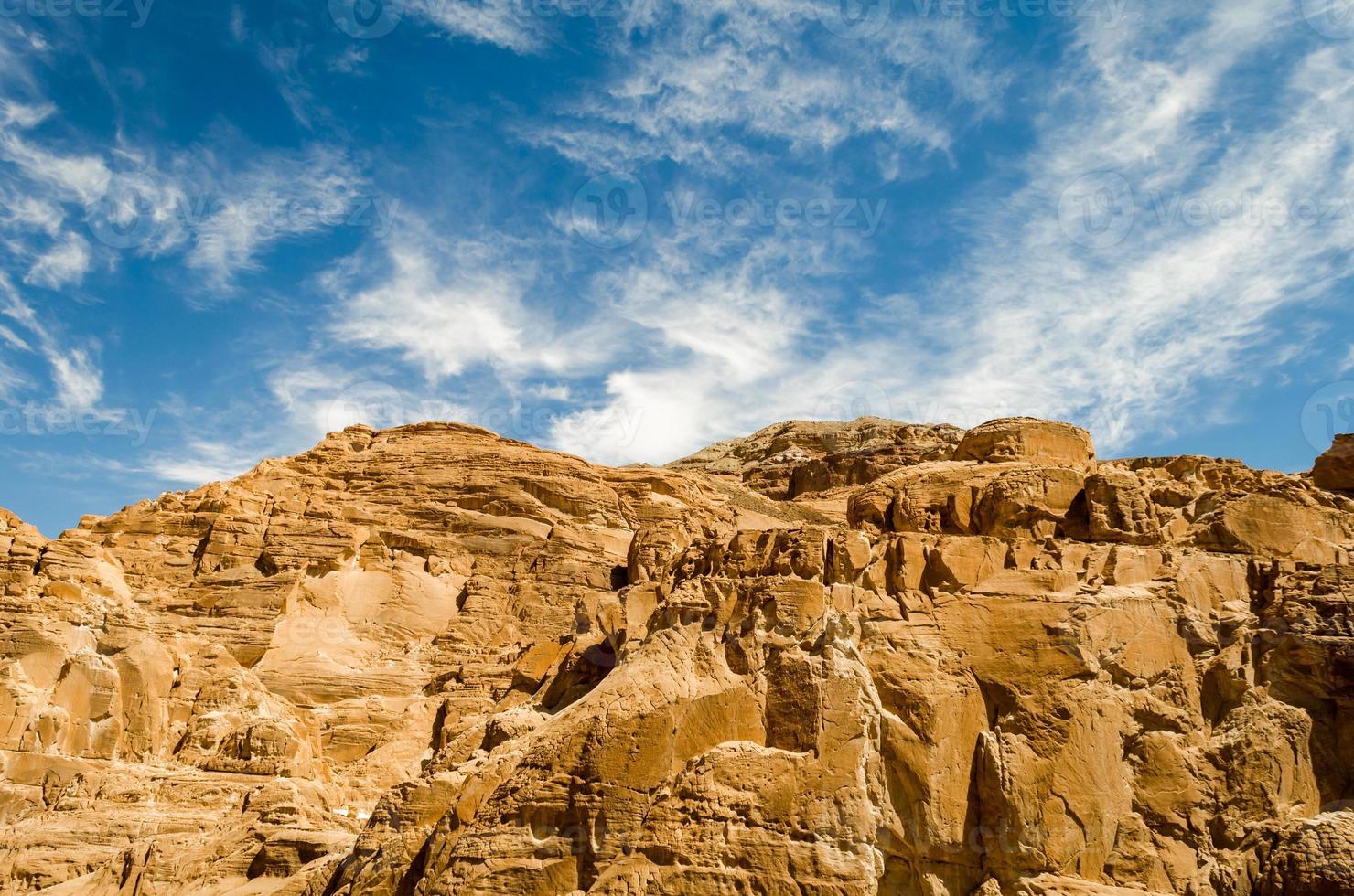 bruine rotsachtige bergen en blauwe hemel met wolken foto