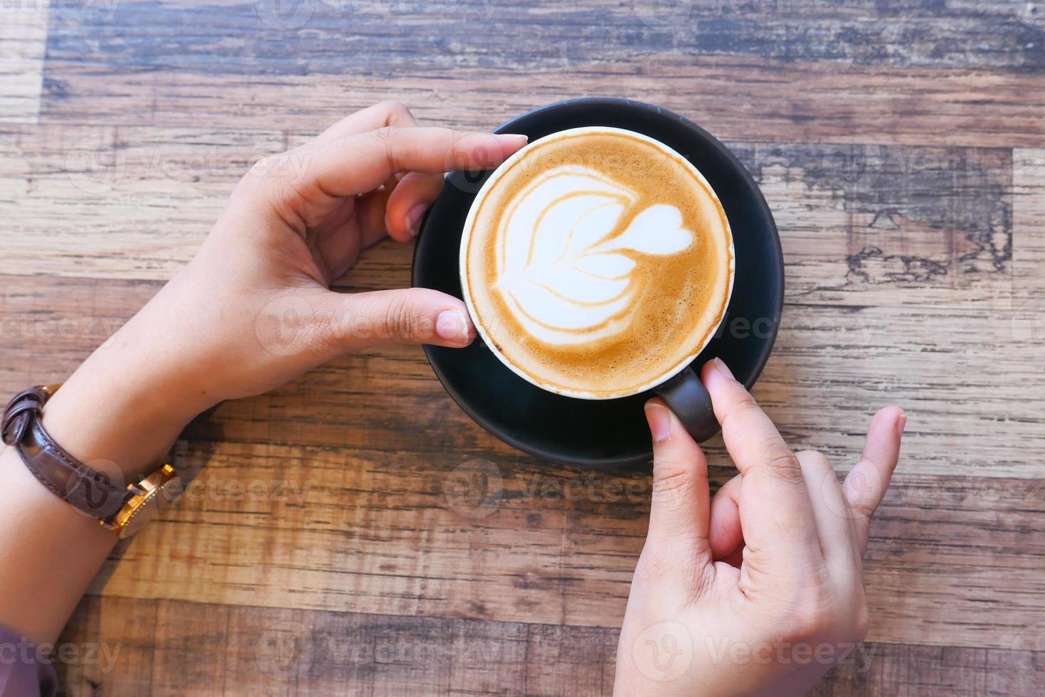 vrouw handen rond een latte foto