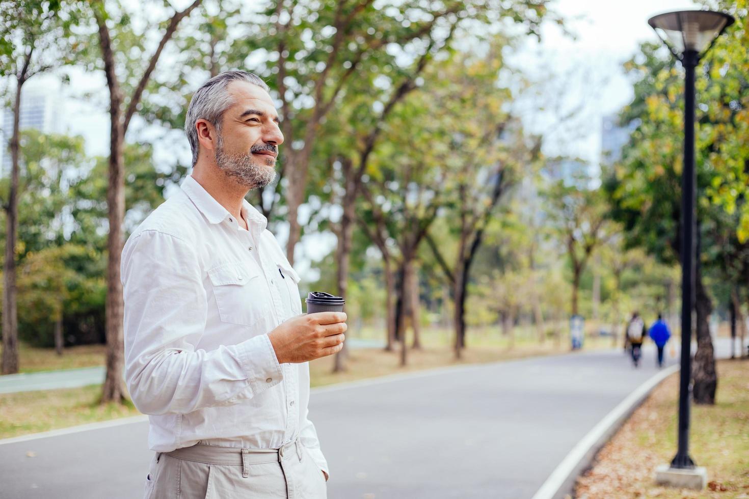volwassen man met koffie in een park foto