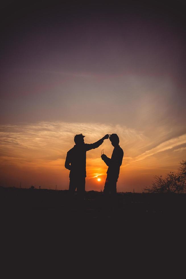 twee vrienden die plezier hebben bij zonsondergang foto