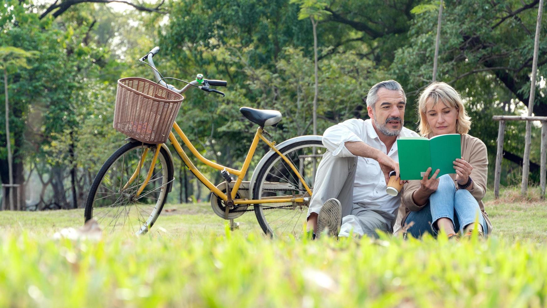 ouder paar lezen van een boek in een park foto