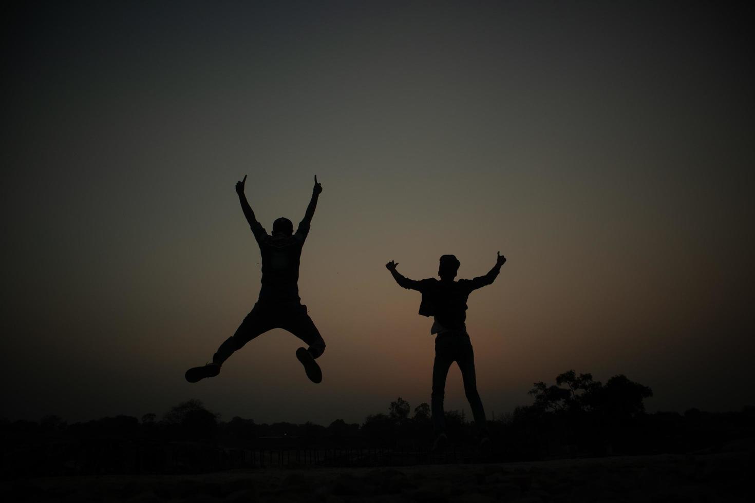 silhouet van twee gelukkige jongens foto