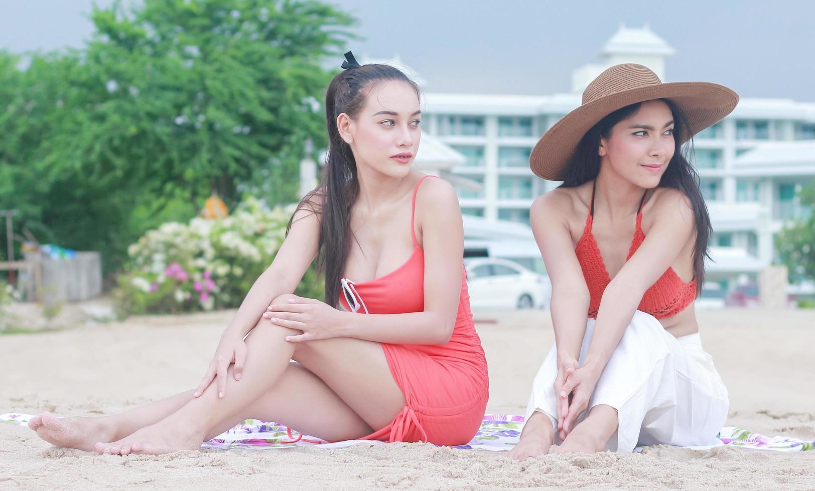 twee mooie vrouwen die gelukkig op het strand zitten foto