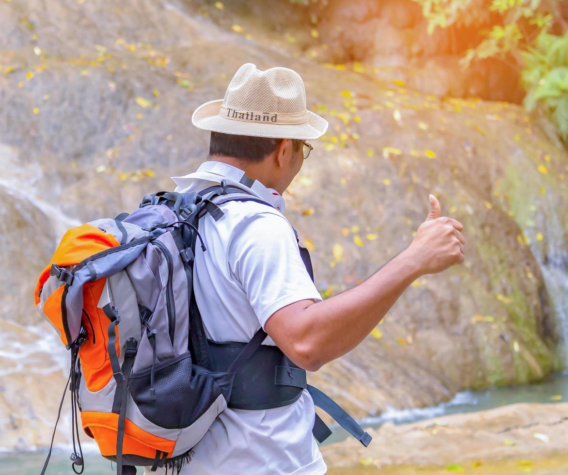 Aziatische reiziger steekt met plezier zijn hand op om frisse lucht in te ademen terwijl hij de natuur bestudeert foto