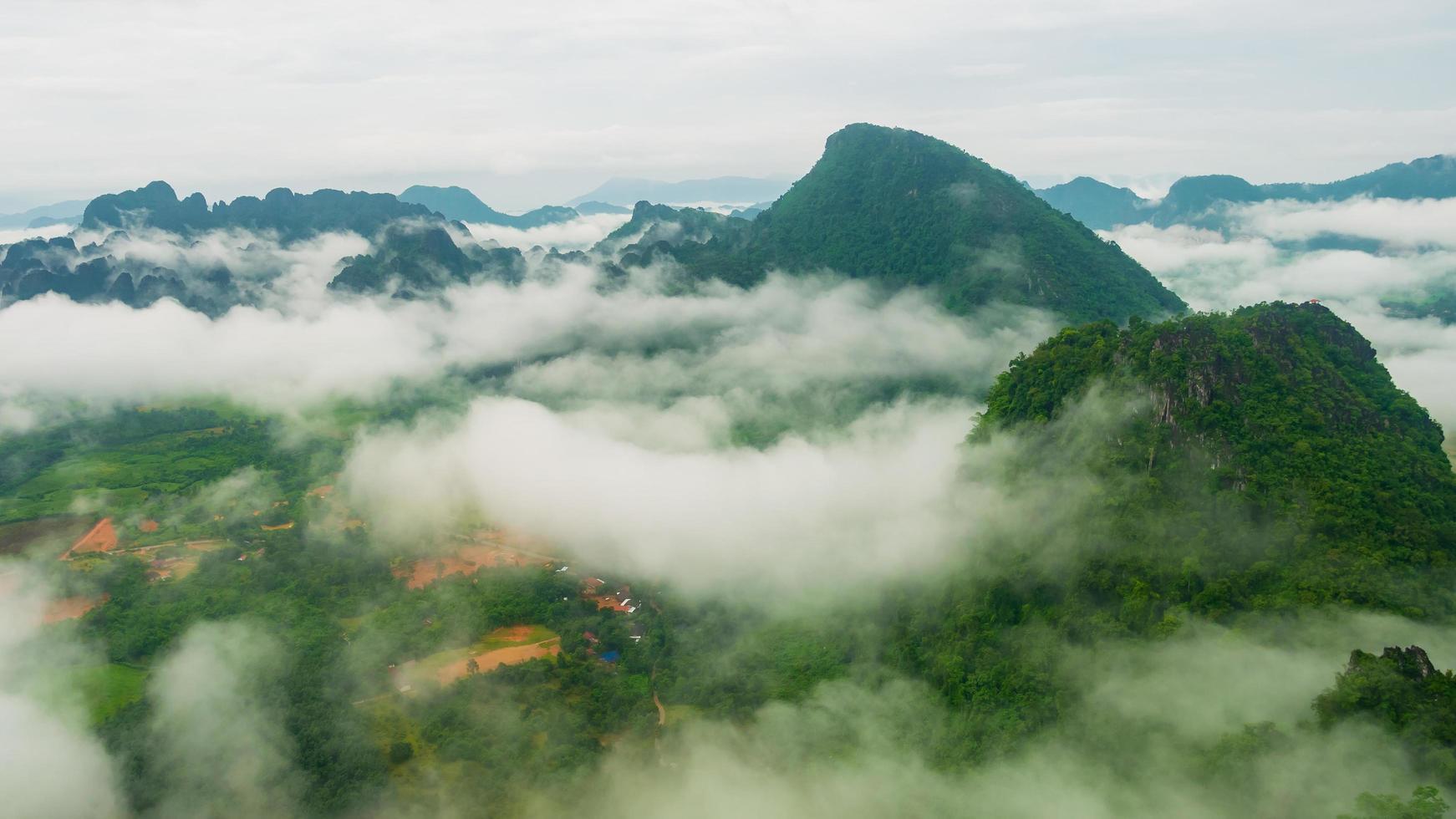 landschapsbergen en blauwe hemel met groene bomen in regenseizoen foto