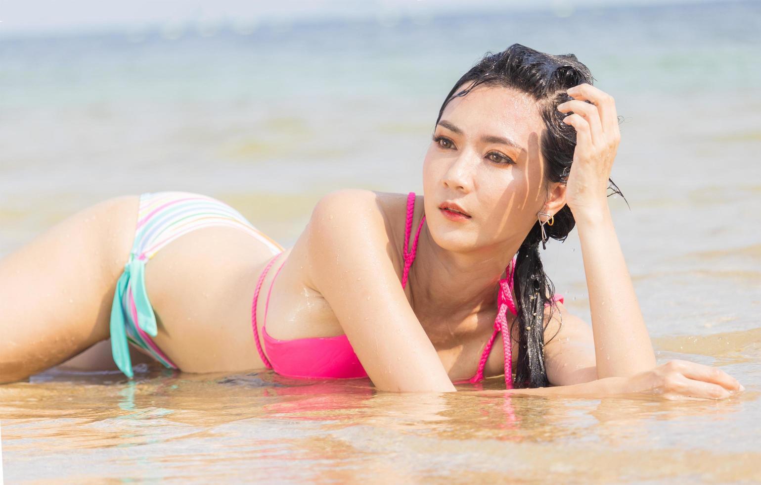 mooie Aziatische vrouw gelukkig loungen op het strand foto