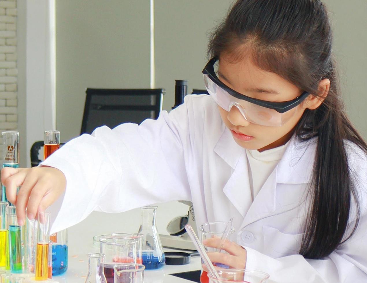 jonge vrouwelijke student doet wetenschappelijke experimenten met een chemische buis in een laboratorium foto