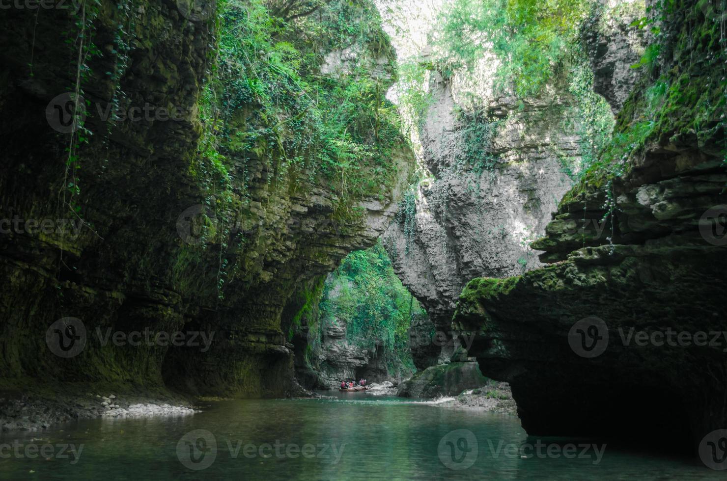 bemoste rotsen en stroom met mensen op een vlot in de verte foto
