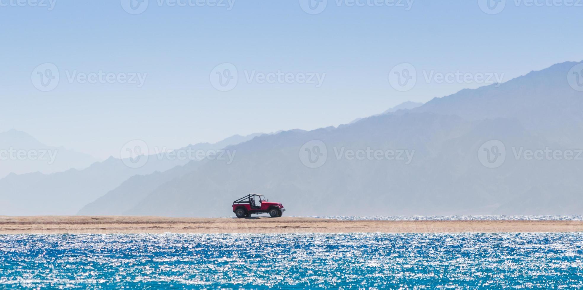 rode jeep op het strand foto