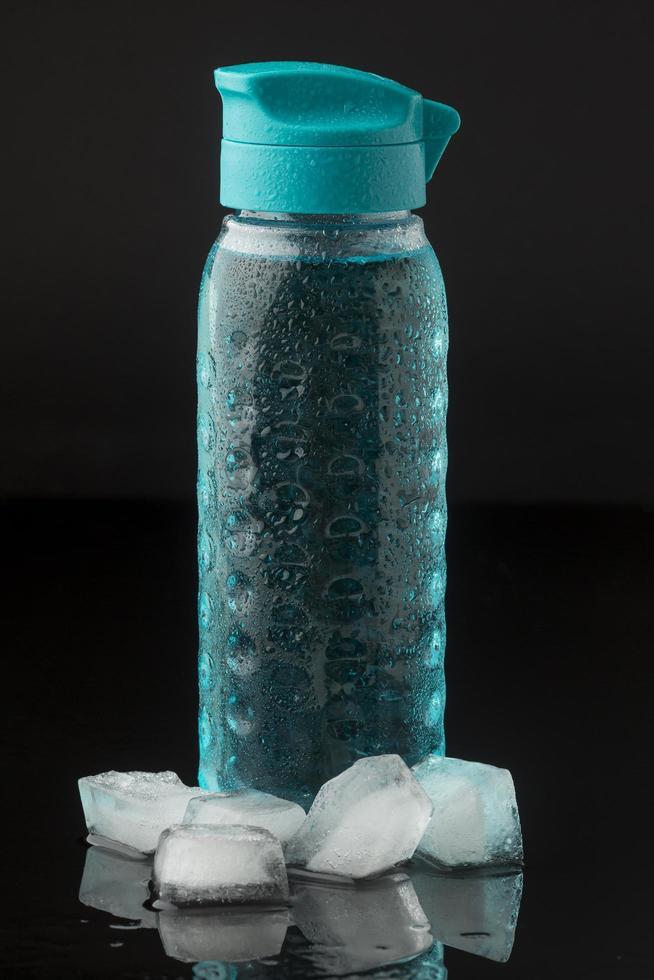 ijsblokjes en flessenwater, vooraanzicht foto