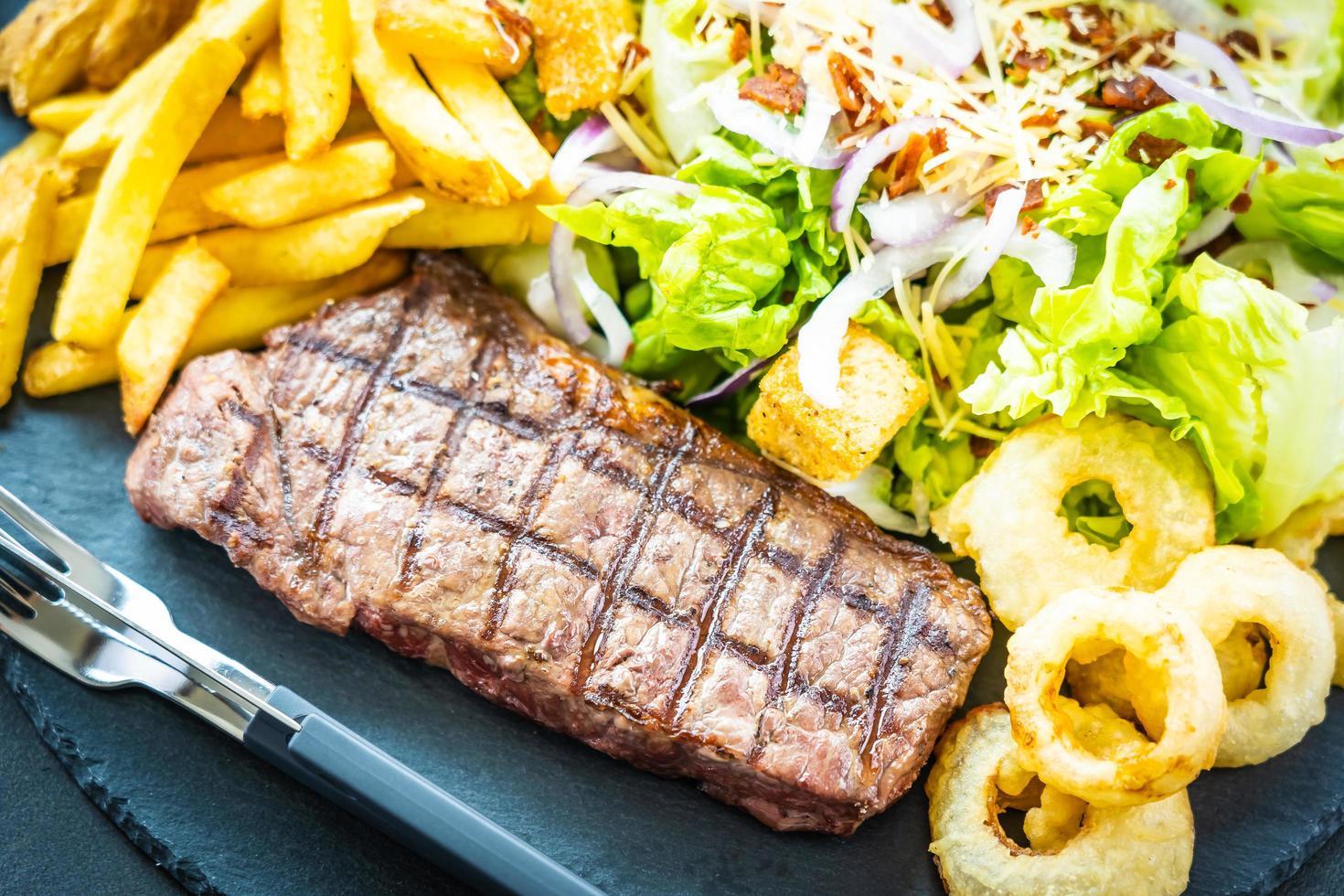 gegrilde biefstuk met frietjes uienring met saus en verse groente foto