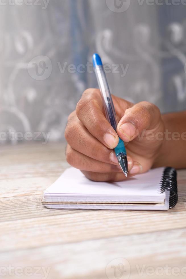 close-up van man schrijven op Kladblok foto