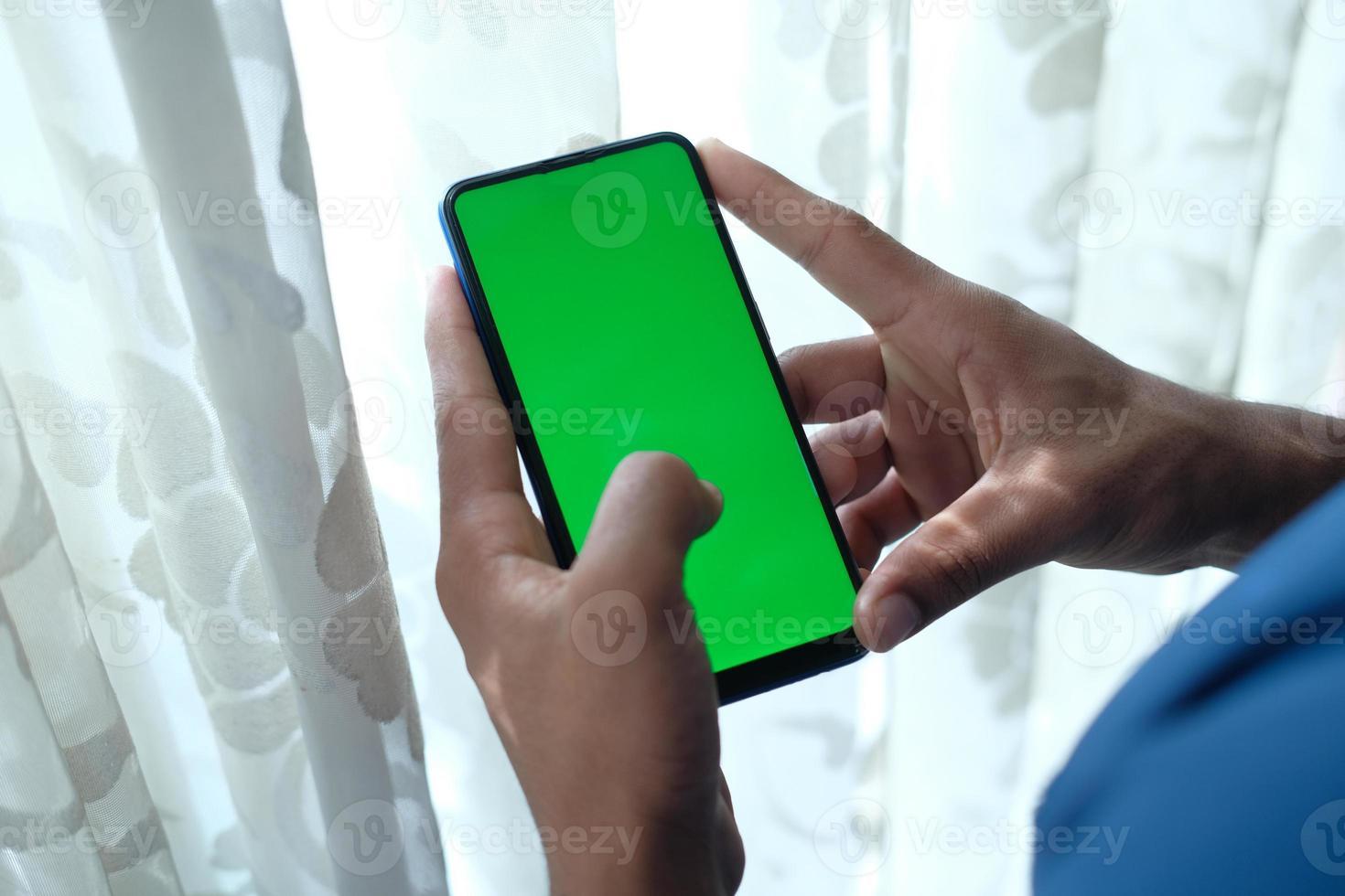 man met behulp van slimme telefoon met groen scherm binnen foto