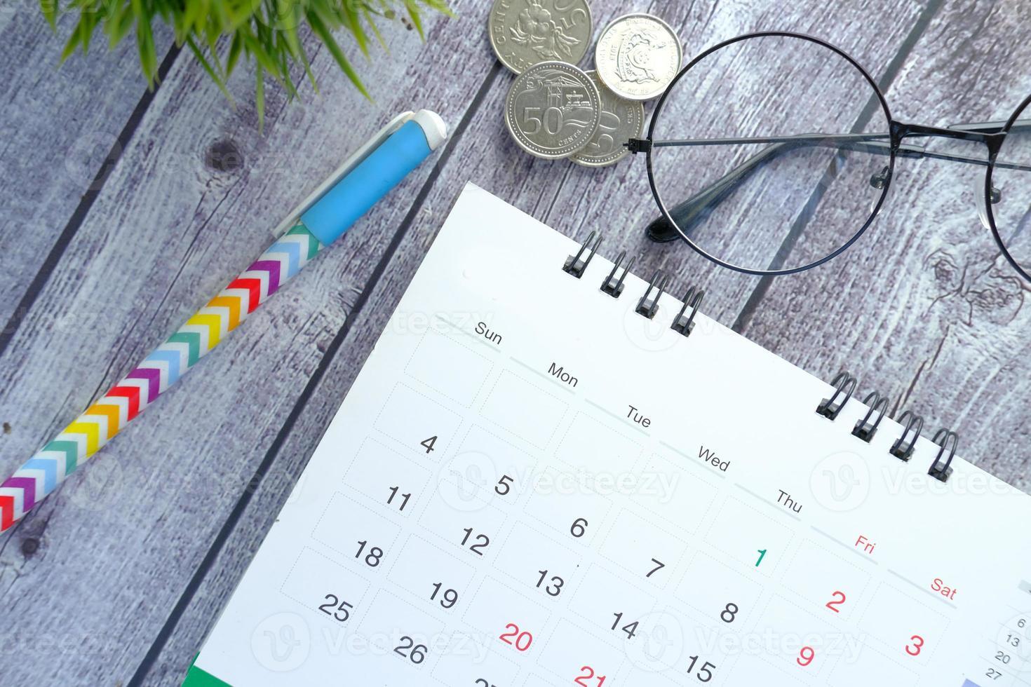 kalender en pen op houten bureau foto