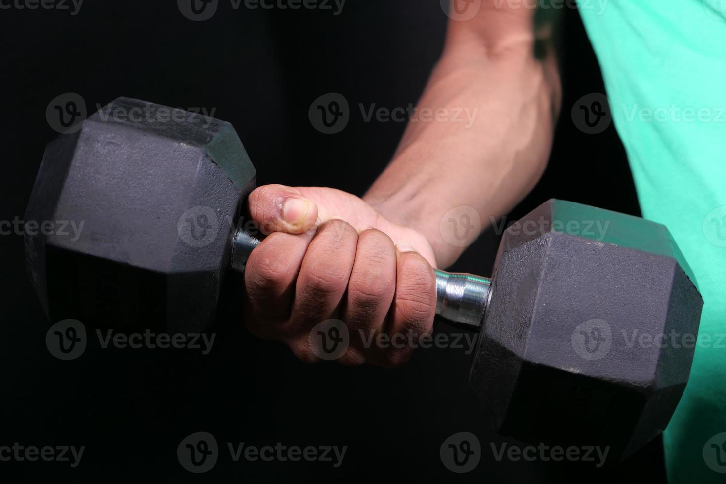 jonge man hand trainen met halters binnenshuis foto