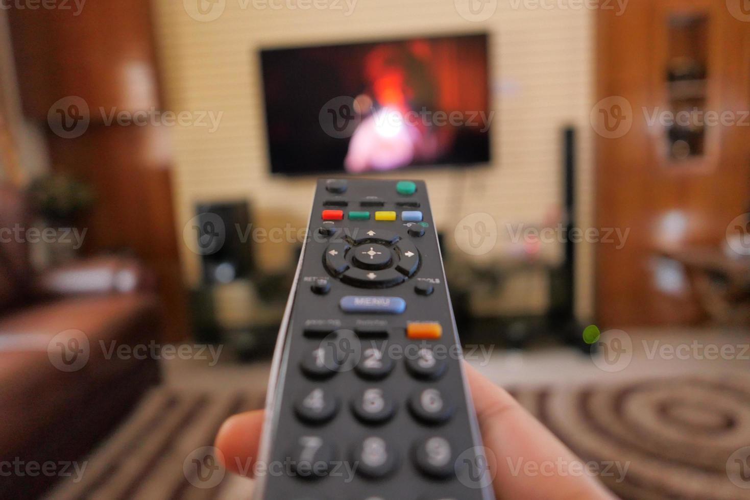 hand met afstandsbediening van de tv in een woonkamer foto