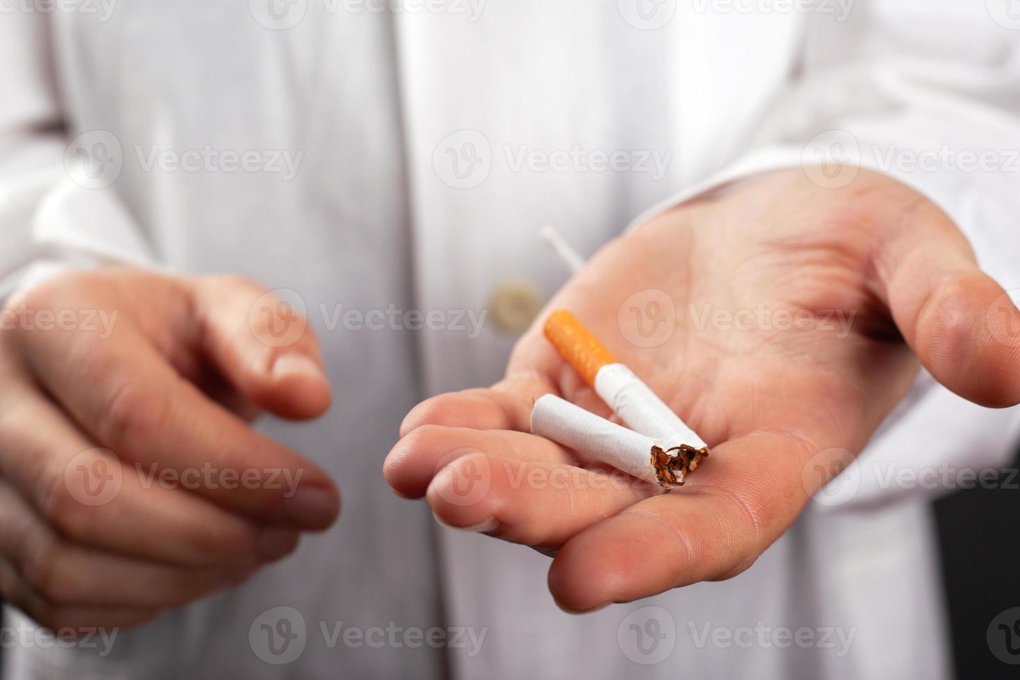 dokter houdt een gebroken sigaret in zijn hand foto