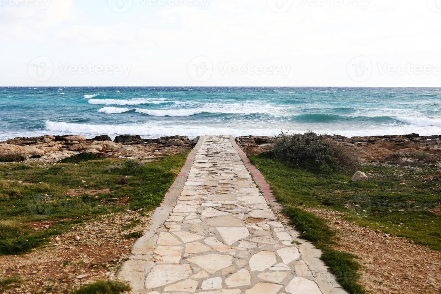betonnen loopbrug die kiezelstenen en een stenen strand kruist. selectieve aandacht foto