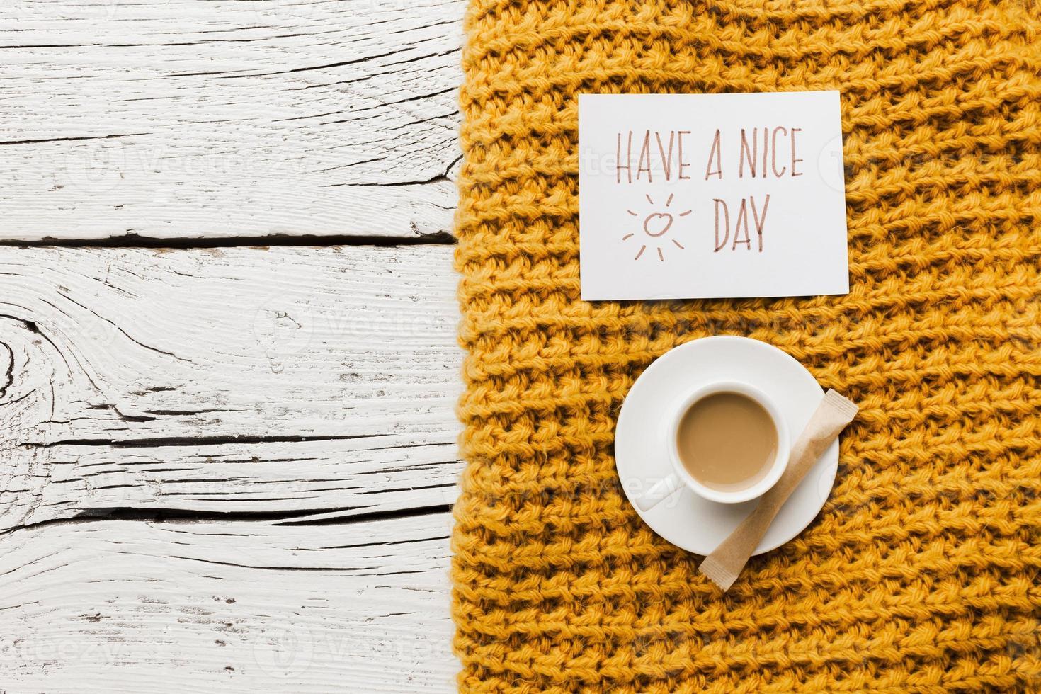 heb een mooie dag bericht met kopje koffie en gele deken op houten achtergrond foto