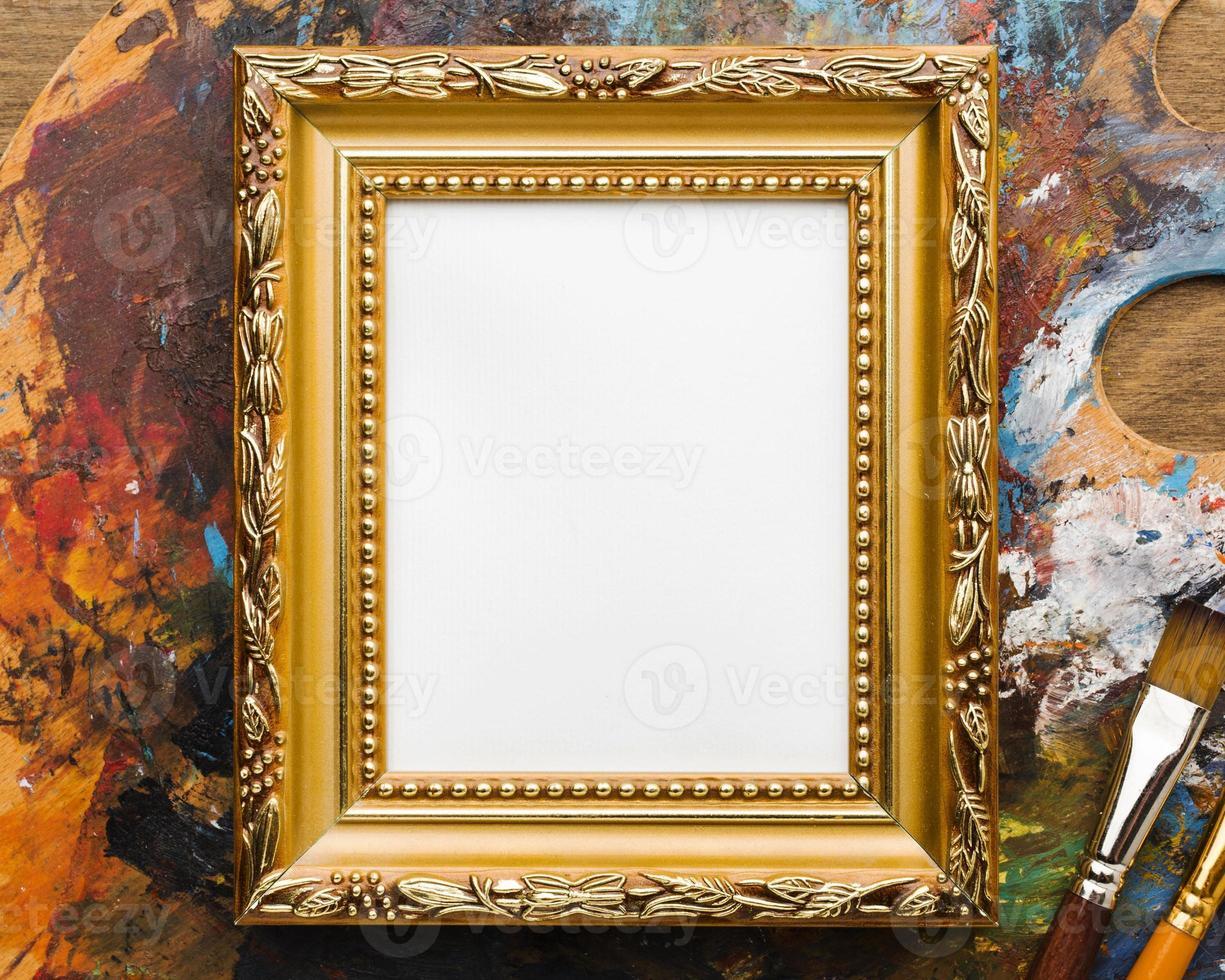 kopieer ruimte canvas met gouden frame en verfsupples foto