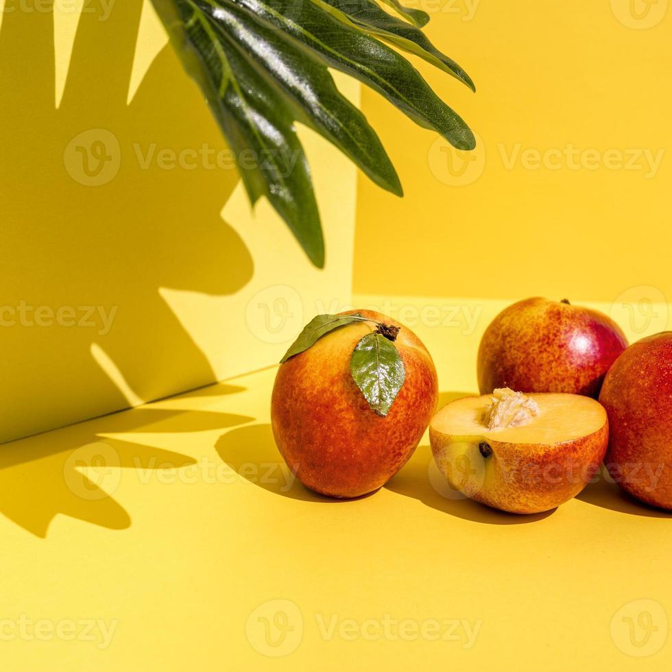 vooraanzicht van heldere perziken met harde schaduwen op dynamische gele achtergrond foto