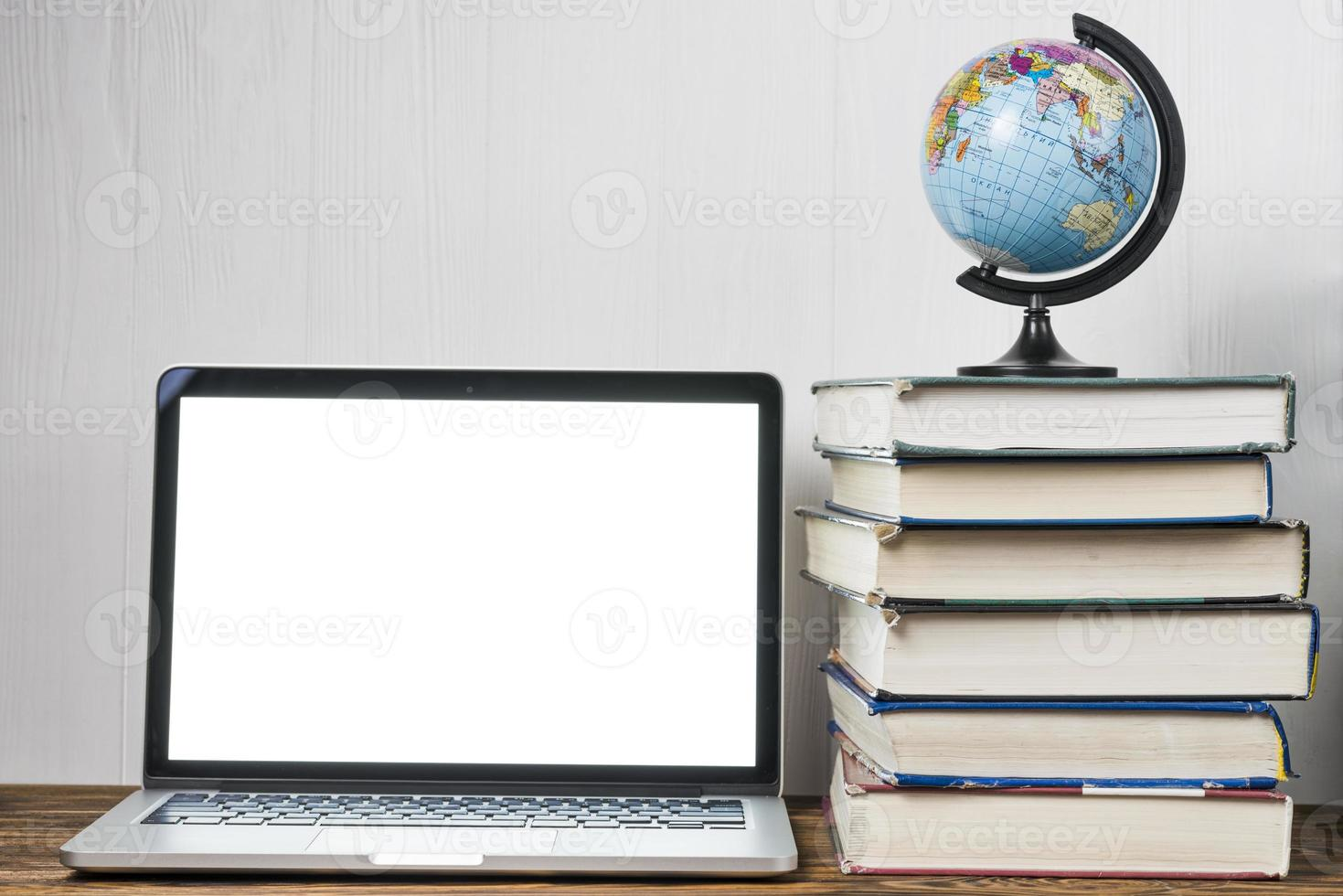 wereldbol en boeken in de buurt van laptop op een tafel foto