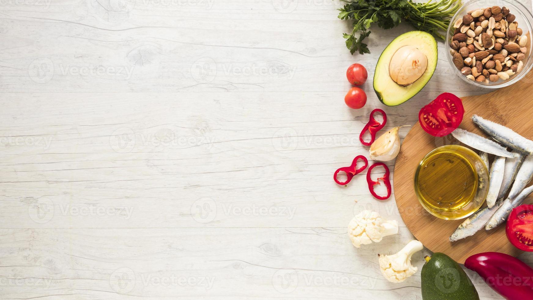 gezonde groenten en gedroogd fruit met olie en rauwe vis op houten tafel foto
