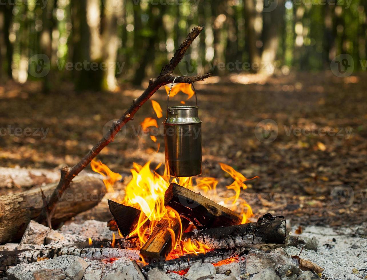 het verwarmen van water bij het kampvuur foto
