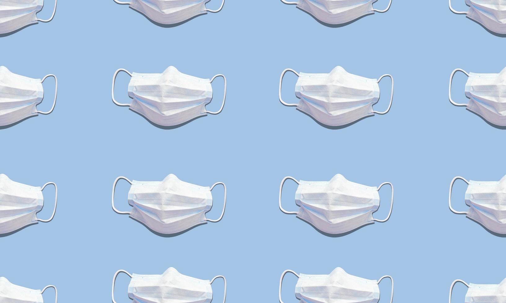 witte medische maskers op blauwe achtergrond. trend naadloos patroon met harde schaduwen. plat leggen stockfoto. foto