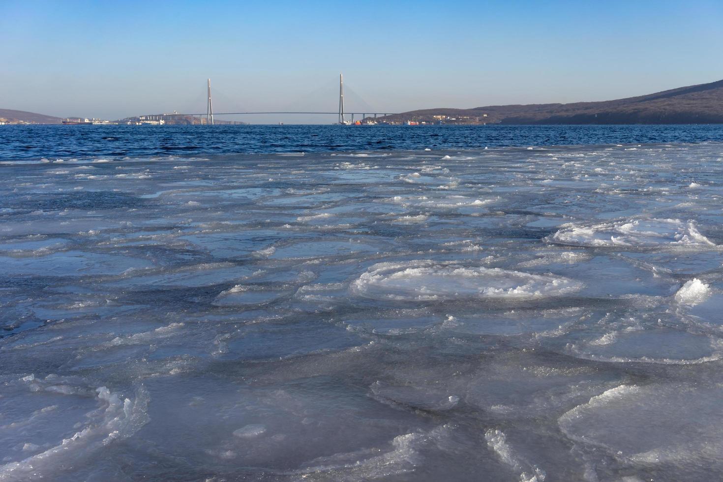 waterlichaam bedekt met ijs en de russky brug op de achtergrond in Vladivostok, Rusland foto
