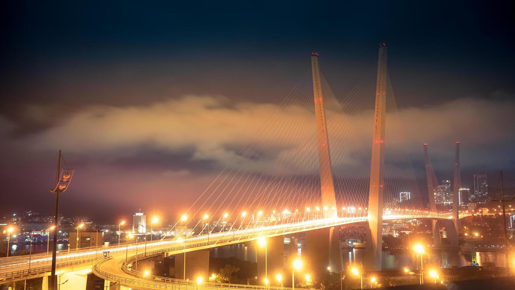 verlicht gouden brug met bewolkte hemel 's nachts in Vladivostok, Rusland foto