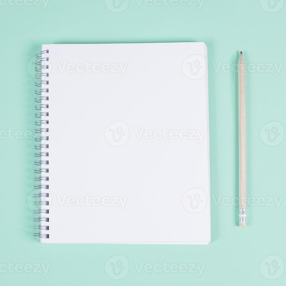 leeg spiraalvormig notitieboekje met potlood op turkooise achtergrond foto