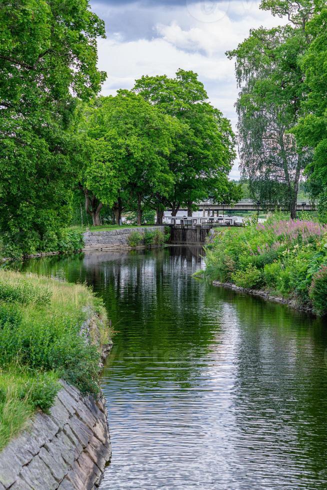 weelderig groen zomerzicht langs het stromsholms-kanaal in Zweden foto