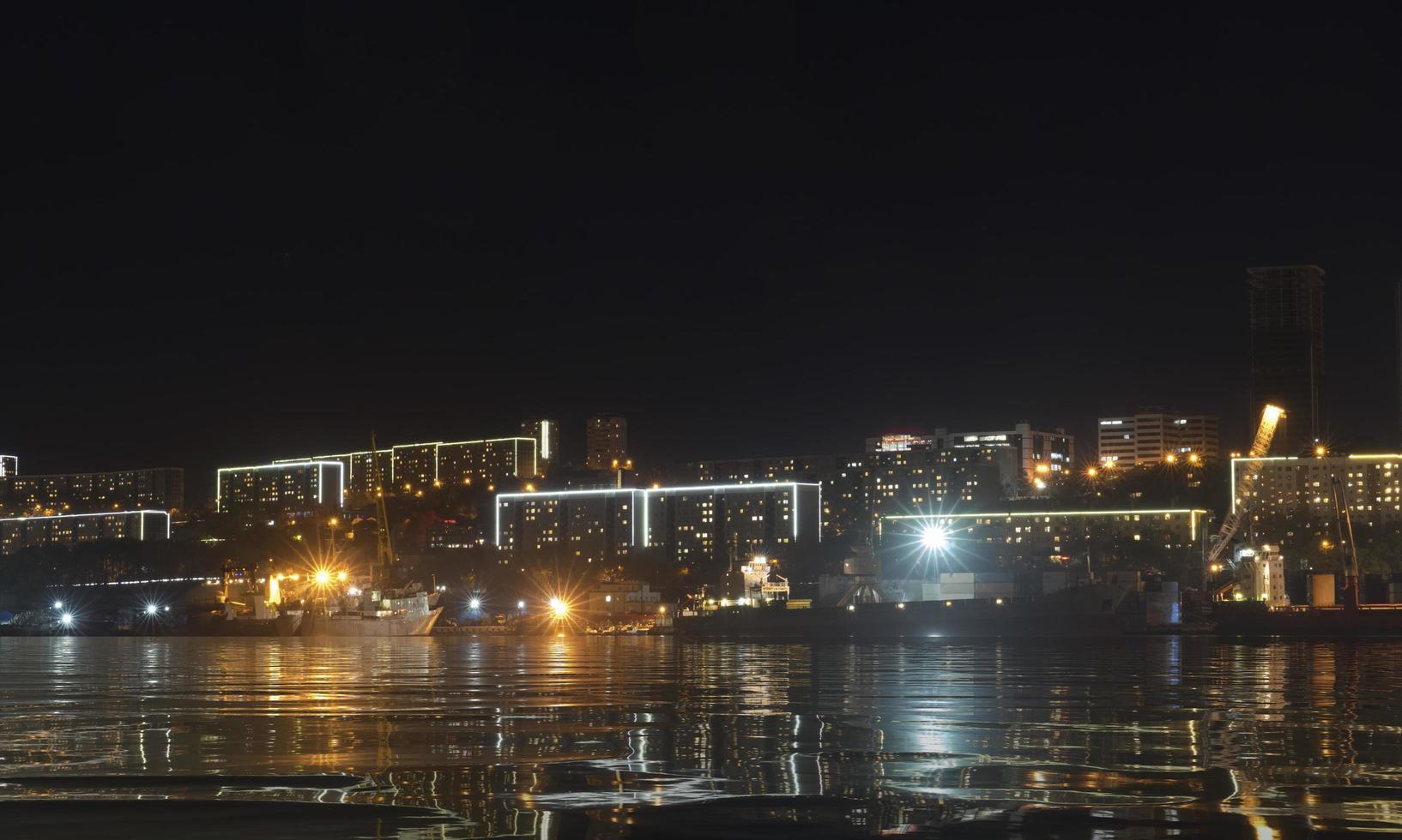 stedelijk landschap met silhouetten van huizen en licht van lantaarns. foto