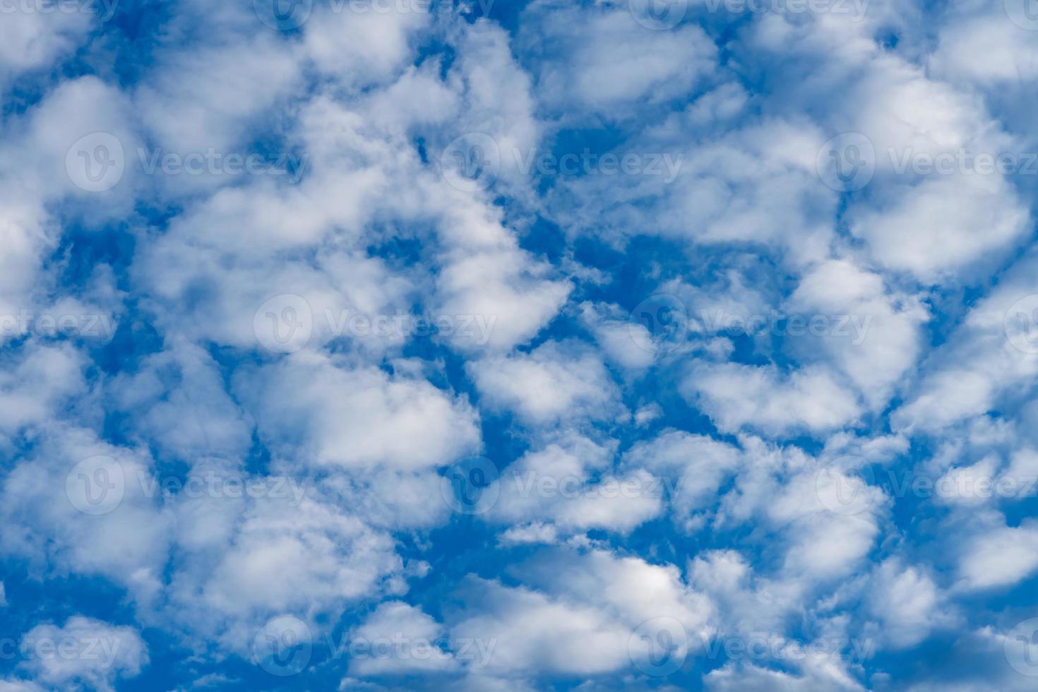 blauwe hemelachtergrond met pluizige witte wolken foto