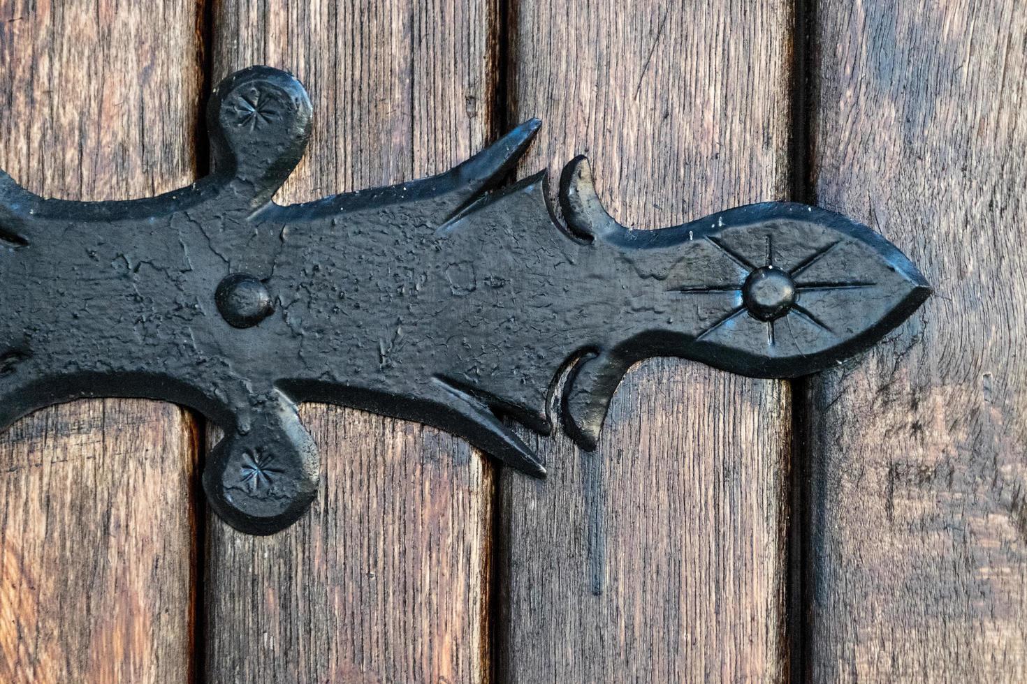 zwart metalen decoratief element op houten deuren foto