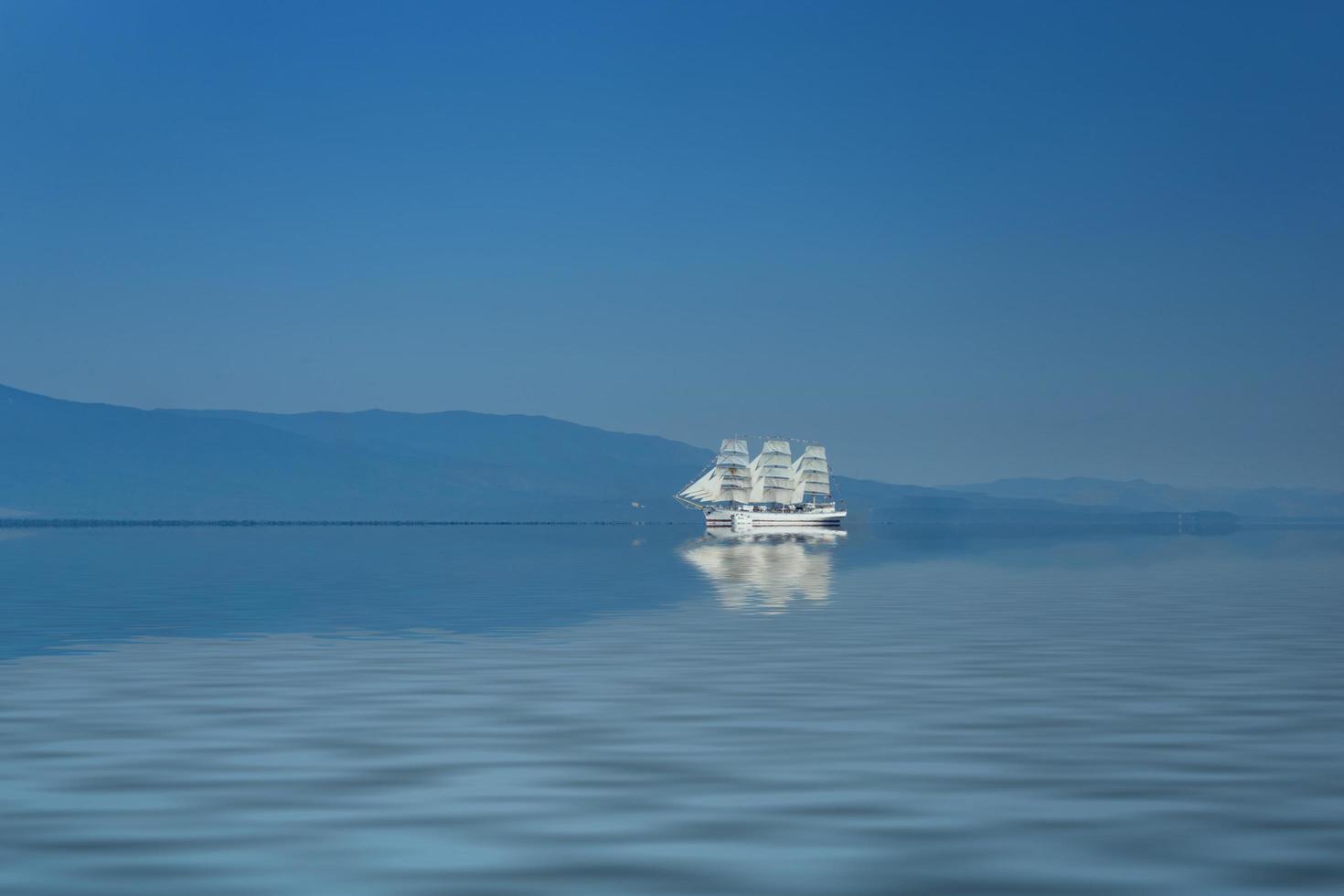 witte zeilboot hoop tegen het zee-landschap foto